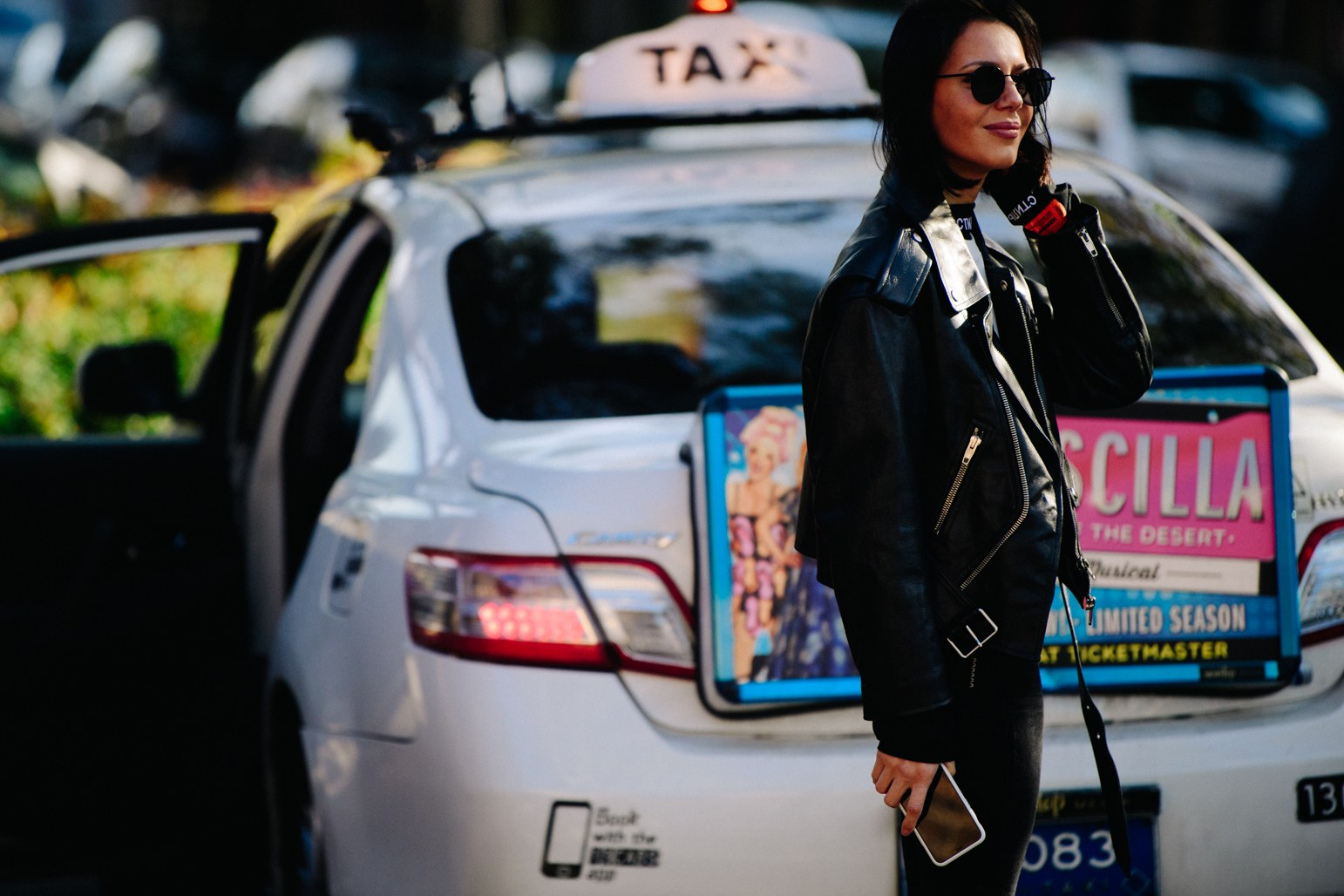 A black hair girl stand with a moto leather jacket, black jeans and round sunglasses