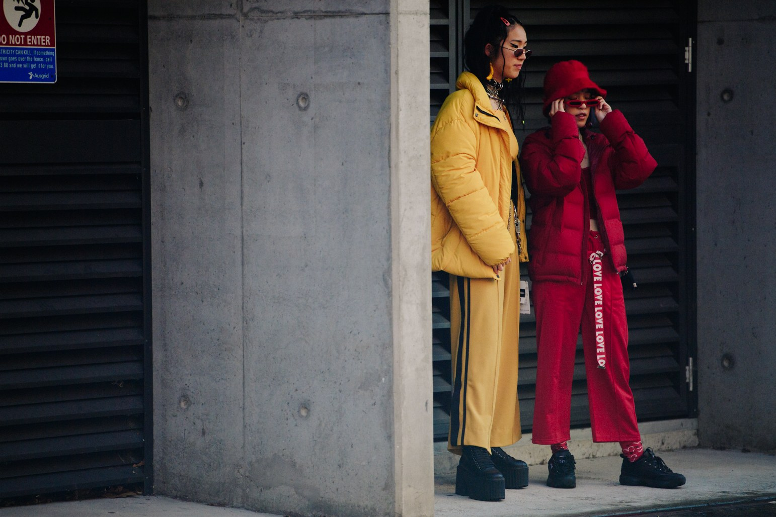"two girls, one all in yellow and the other in red. They wear puffer jackets and side-striped pants of their own colour. they both wear black ""ugly dad sneakers""."